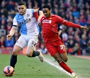 Liverpool's Raheem Sterling is held off by Craig Conway of Blackburn